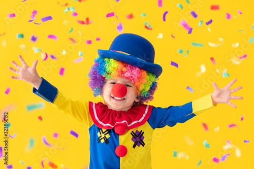 Fotografija Funny kid clown playing against yellow background