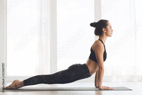 Fotomural Woman doing cobra pose at modern studio