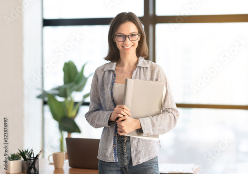 Happy manager smiling at camera in modern office