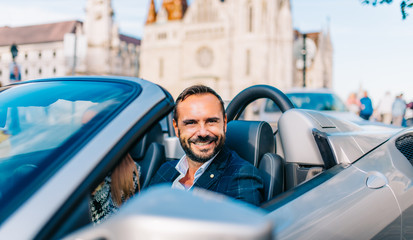 Successful happy businessman sitting in convertible super car