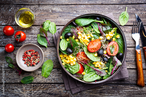 Fotografia Healthy salad, leaves mix salad with mangold, spinach and vegetables in the plate over wooden background, top view