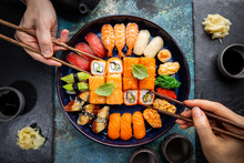 Set Of Sushi And Maki With Soy Sauce With Human Hands Over Blue Background. Top View With Copy Space