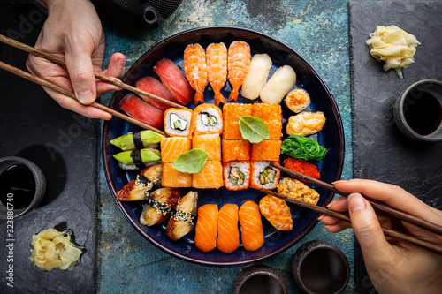 Fototapeta Set of sushi and maki with soy sauce with human hands over blue background. Top view with copy space obraz