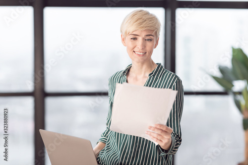 Businesswoman Working With Documents Sitting On Desk At Workplace