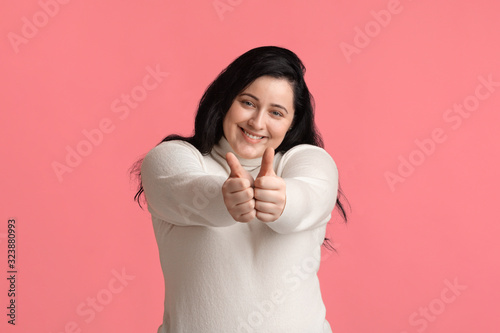 Pretty Plump Woman Showing Thumbs Up At Camera And Sincerely Smiling