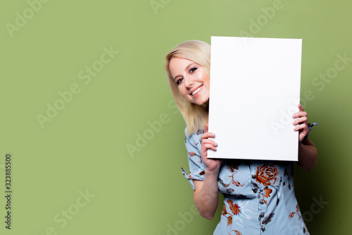 Fototapeta Blonde woman with white banner on green background