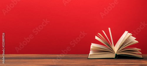 Obraz na plátně Open book  on red background. text place .