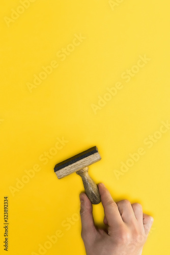 top view of man holding stamp isolated on yellow, quality concept