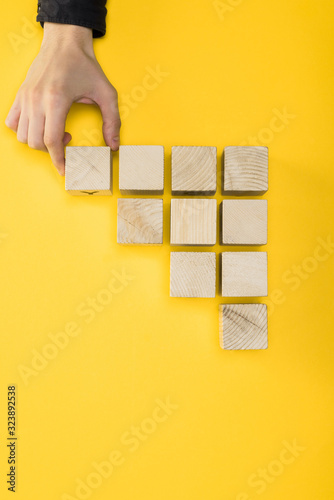 top view of man touching wooden cube isolated on yellow