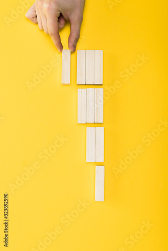 top view of man holding wooden block isolated on yellow