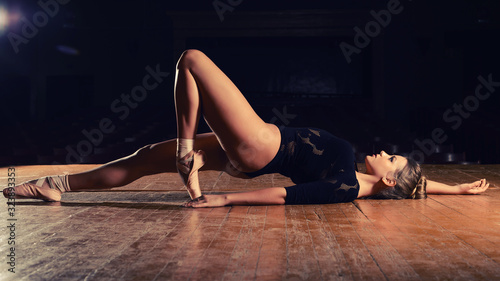 Photo ballerina in pointe shoes is lying her back bent leg