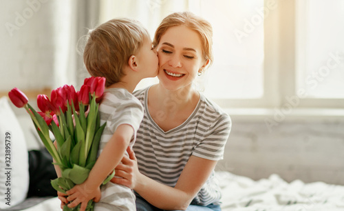 Leinwand Poster happy mother's day! child son gives flowers for  mother on holiday