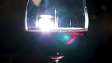Creatively Lit Glass Of Sparkling Wine With Perlage Effect On Black Background. Stock Footage. Close Up Of Red Sparkling Wine Inside A Glass.