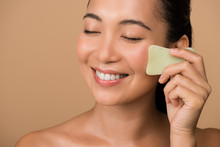 Smiling Beautiful Naked Asian Girl With Closed Eyes Using Facial Gua Sha Jade Board Isolated On Beige