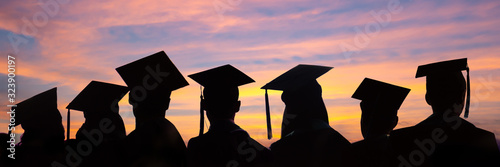 Fototapeta Silhouettes of students with graduate caps in a row on sunset background. Graduation ceremony at university web banner. obraz