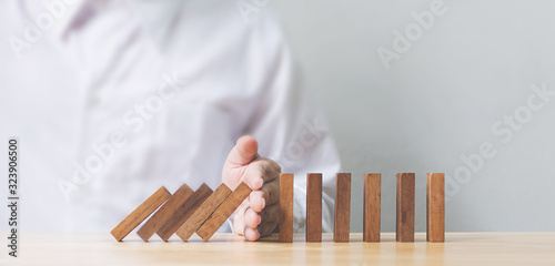 Cuadros en Lienzo Hand stopping wooden domino business crisis effect or risk protection concept