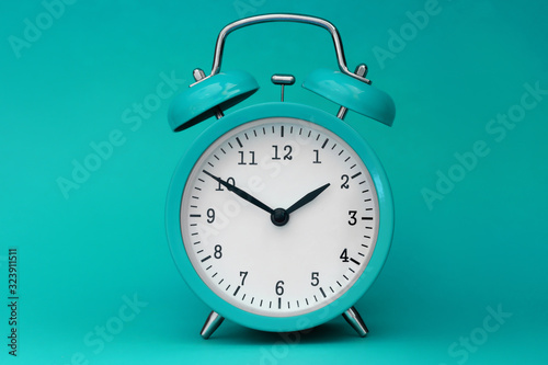 Obraz Modern alarm clock turquoise closeup object. Time online system concept - fototapety do salonu