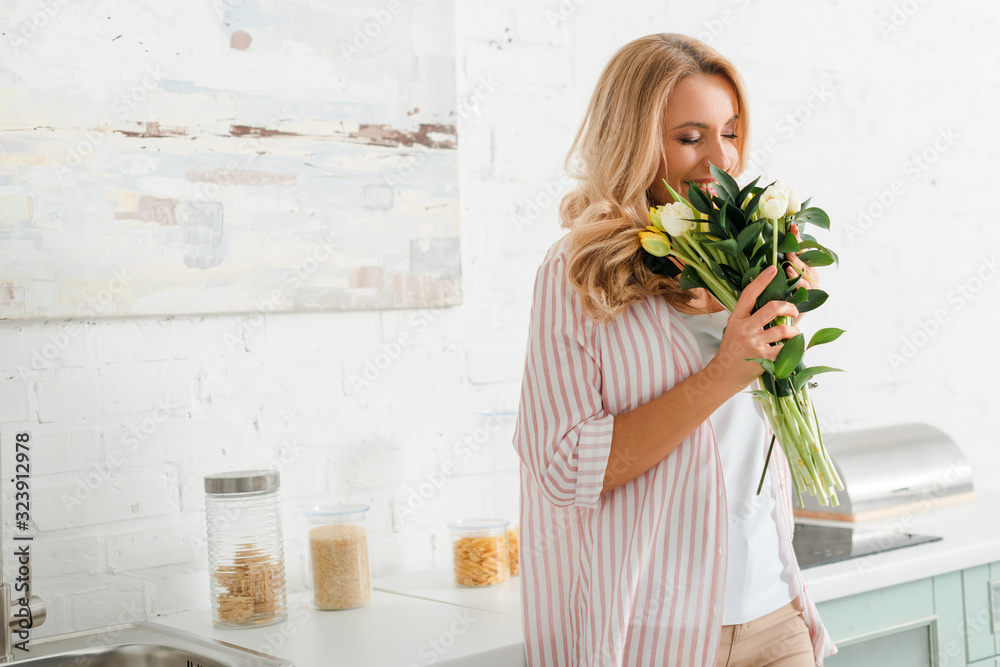 Fototapeta happy woman smelling bouquet of tulips at home