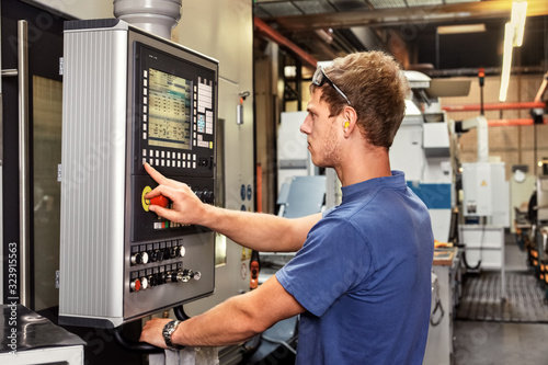 Skilled worker controlling a digitally programmed machine tool Fototapete