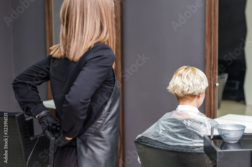 Photo The professional female hairdresser puts on black apron to dye the woman's hair in the hair salon