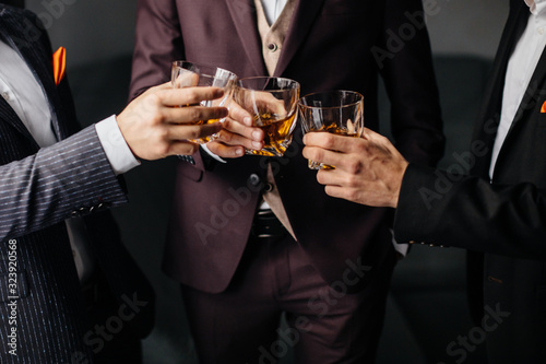 Tablou Canvas Close-up partial view of three friends clink glasses of whiskey drink, alcoholic beverage