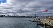Slow Motion pan of Halifax Harbour from Dartmouth Alderney ferry terminal with waving Canadian Flag and storm clouds in distance