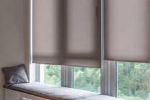 Motorized Roller Shades. Automatic Roller Blinds Beige Color On Large Windows. Remote Control Shades Are Near The Sofa With The Pillow. Sofa Covered With Pastel Velours. Summer. Green Trees Outside.