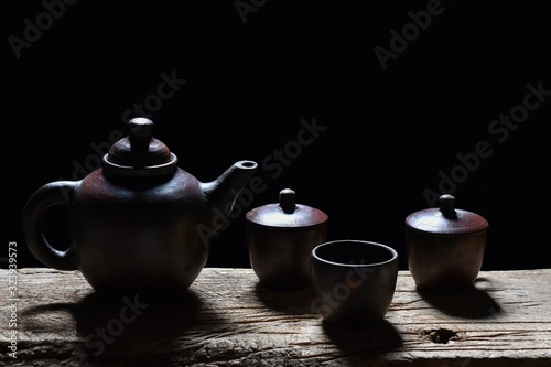Hot tea in a teapot, glass and cup on a black background Canvas Print