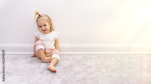 Valokuvatapetti Cute bare foot baby girl in pink trousers sits near white wall on grey rug, smil