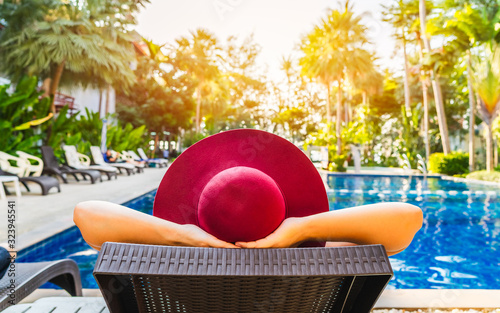 Carta da parati Summer lifestyle traveler woman relaxing in front of modern luxury swimming pool