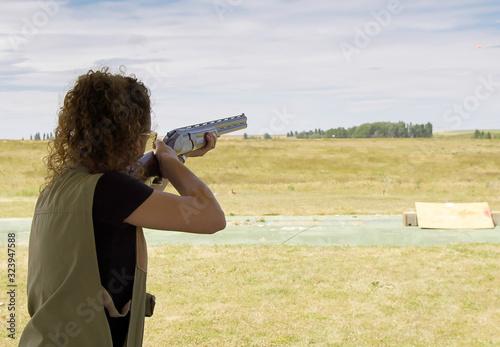 mujer joven practicando el deporte de tiro al plato al aire libre Canvas Print