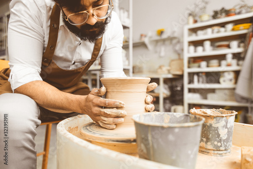 A young male potter is engaged in craft in his workshop on a potter's wheel and Fotobehang