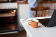 Workplace with cup of coffee, laptop, and notebook. Freelancer home office in cozy kitchen. Concept of female business, working woman, housekeeping and using oven. Close up.