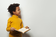 Curious Black Child Boy Reading A Book On White Background