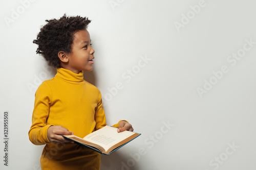 Obraz Curious black child boy reading a book on white background - fototapety do salonu
