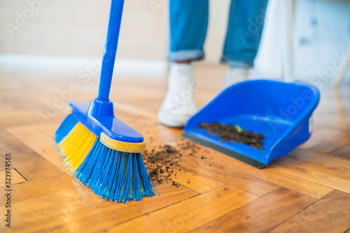 Fotografering Latin man sweeping wooden floor with broom at home.