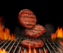 Falling Down Beef Cutlets For Burgers. Meat Roasted On Metal Barbecue BBQ Grill With Flaming Fire And Ember Charcoal On Black Background. Close Up