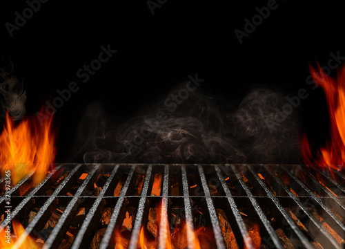 Hot empty portable barbecue BBQ grill with flaming fire and ember charcoal on black background Fotobehang