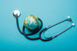 Globe and stethoscope on blue background, world health day concept