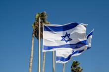 Israeli Flags Flying Against A Blue Sky