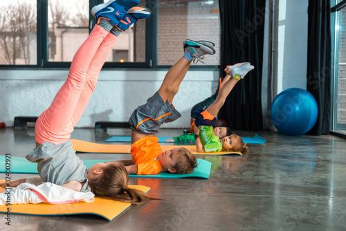 Selective focus of multiethnic children raising legs on fitness mats in gym