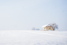 White Landscape Of Lonely Small House With Snowy Roof In Empty Smooth White Valley Under Endless Sky