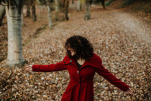 From Above Of Curly Haired Woman Smiling On Golden Fallen Leaves On Blurred Background