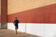 Side View Fit Hispanic Sporty Man In Active Wear Listening Music While Jogging Along City Street In Dallas