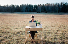 Travelling Woman Working On A Laptop And Desk In A Field Outside