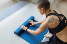 Short Haired Tattooed Woman Unrolling Yoga Mat, Preparing For Yoga Pra