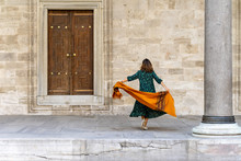 Woman In Green Dress And Orange Scarf Exploring Istanbul On Vacation