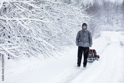 Adult man pulling sledge in the snow during strong snowfall Poster Mural XXL