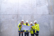 A group of engineers standing against concrete wall on construction site.