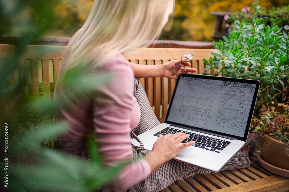 Fototapeta Senior woman architect with laptop sitting outdoors on terrace, working.